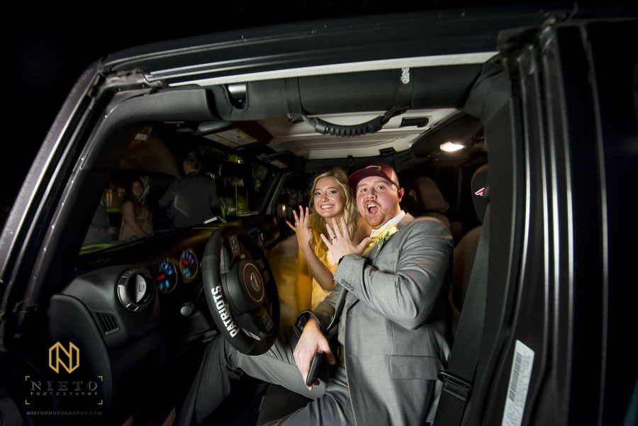 bride and groom showing their rings hands as they drive away