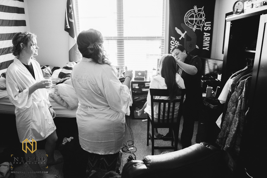 black and white image of bridesmaids watching the bride having her makeup done