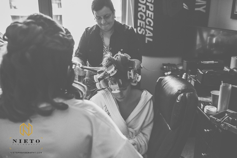 black and white image of hair stylist curling the brides hair