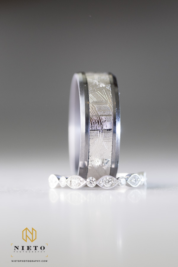 detail shot of the grooms wedding band standing on its side inside of the brides wedding band