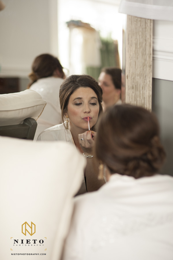 bridesmaid looking in a mirror putting on lip gloss