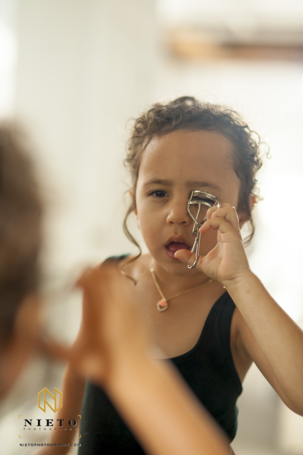 a flower girl using a mirror trying to curl her eye lashes