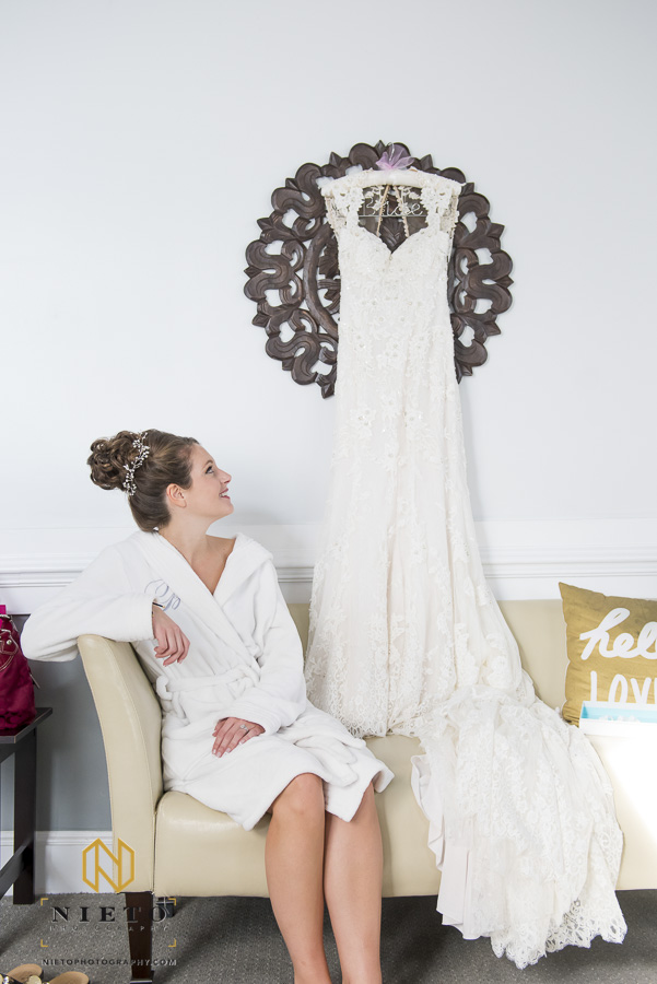 bride looking at her wedding gown as she sits in her robe
