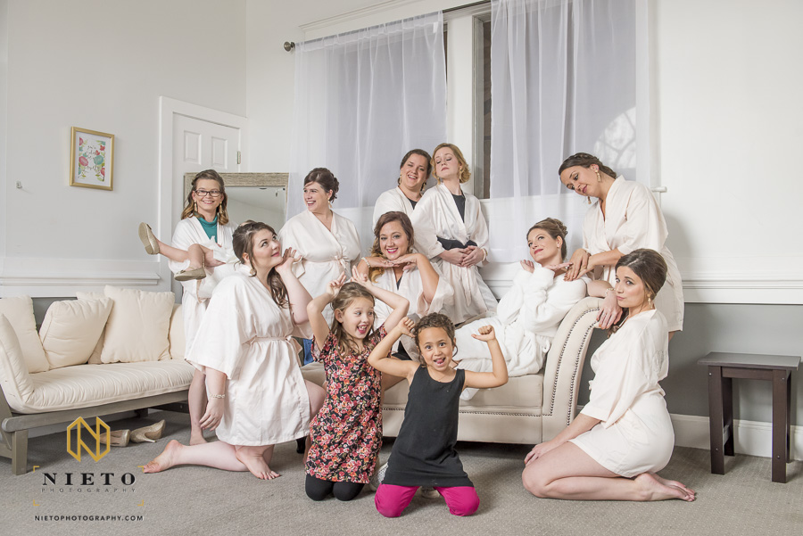 silly portrait of the bride and her bridesmaids in their robes posing in the bridal suite at Market Hall