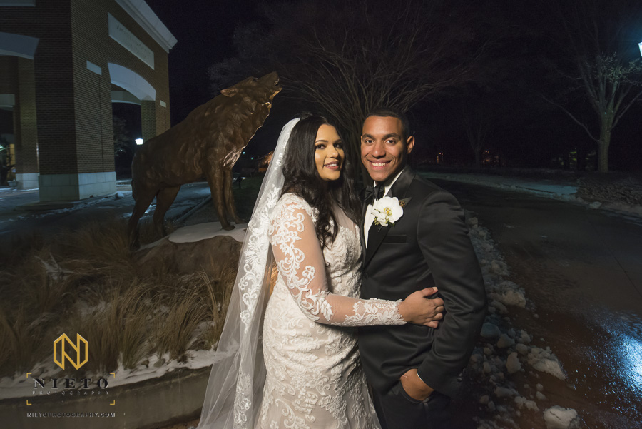 bride and groom posing in front of wolf statue outside of the Park Alumni Center