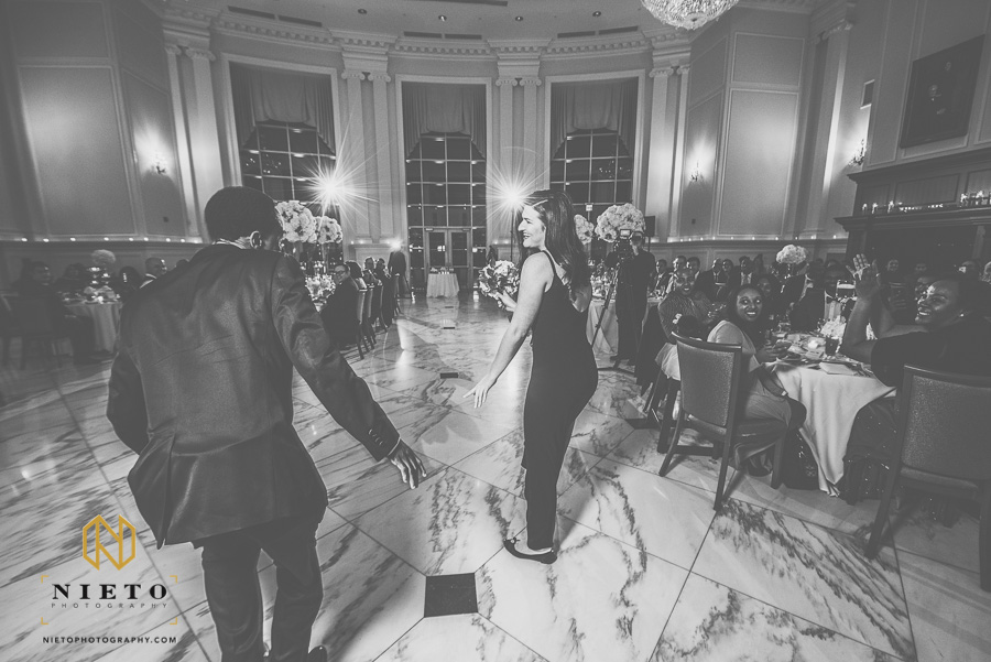 black and white picture of bridesmaid and groomsman entering the banquet hall at Park Alumni center