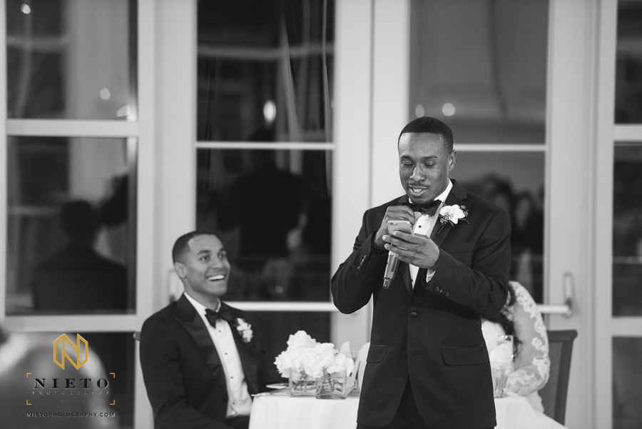 Black and white image of the best man reading his toast of his phone as the groom is behind him smiling