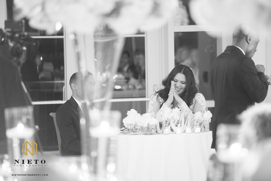 black and white image of the bride laughing as the best man gives a toast