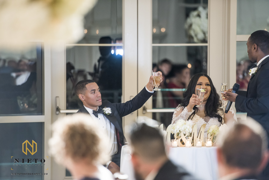 groom raises his glasses as the best man finishes his wedding toast