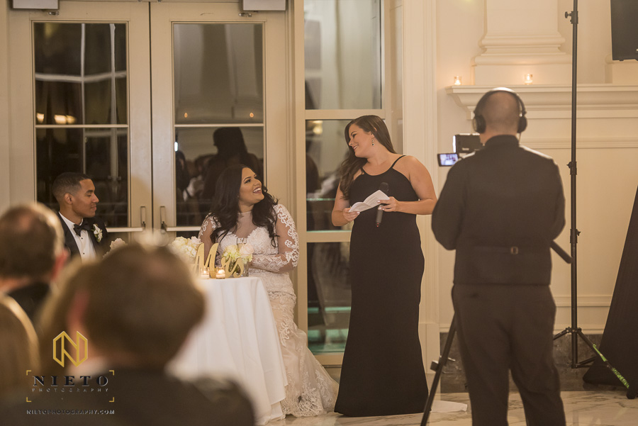 bride and maid of honor smile at each other as the maid of honor gives her toast