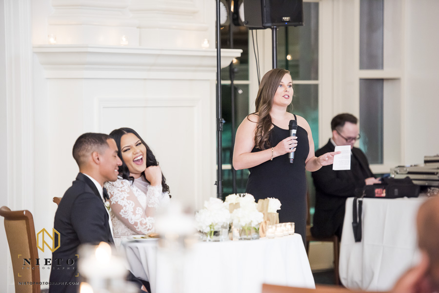 maid of honor giving a wedding toast as bride and groom laugh