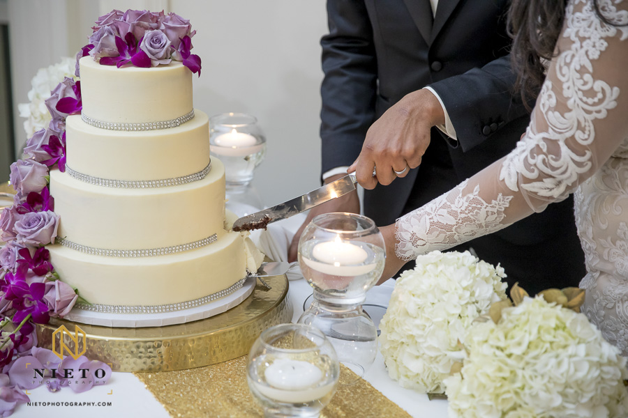 close up of bride and grooms hands as they cut their wedding cake