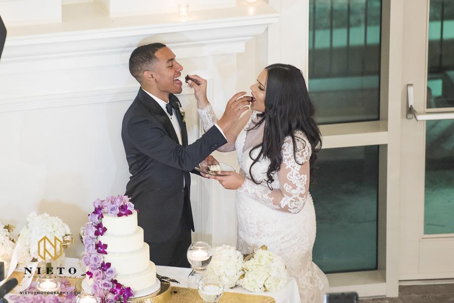 bride and groom feeding each other cake at their Park Alumni Center wedding reception
