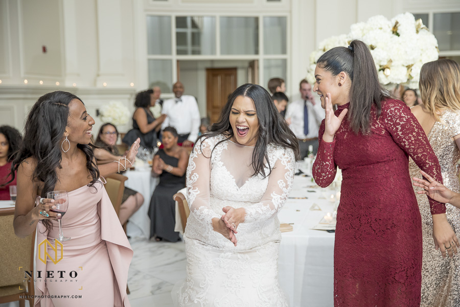 bride laughing while talking to wedding guest