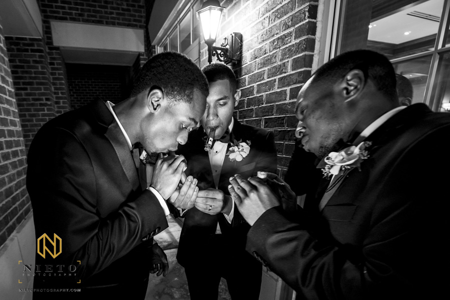 black and white image of the groom and groomsmen lighting cigars together