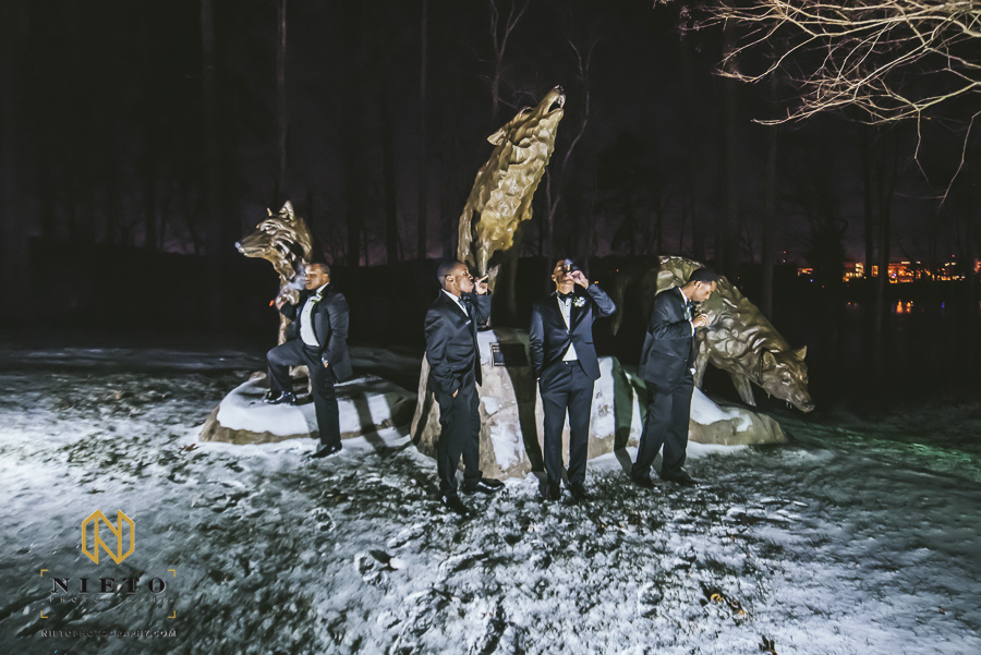 groom and groomsmen smoking cigars around wolf statues outside of Park Alumni Center