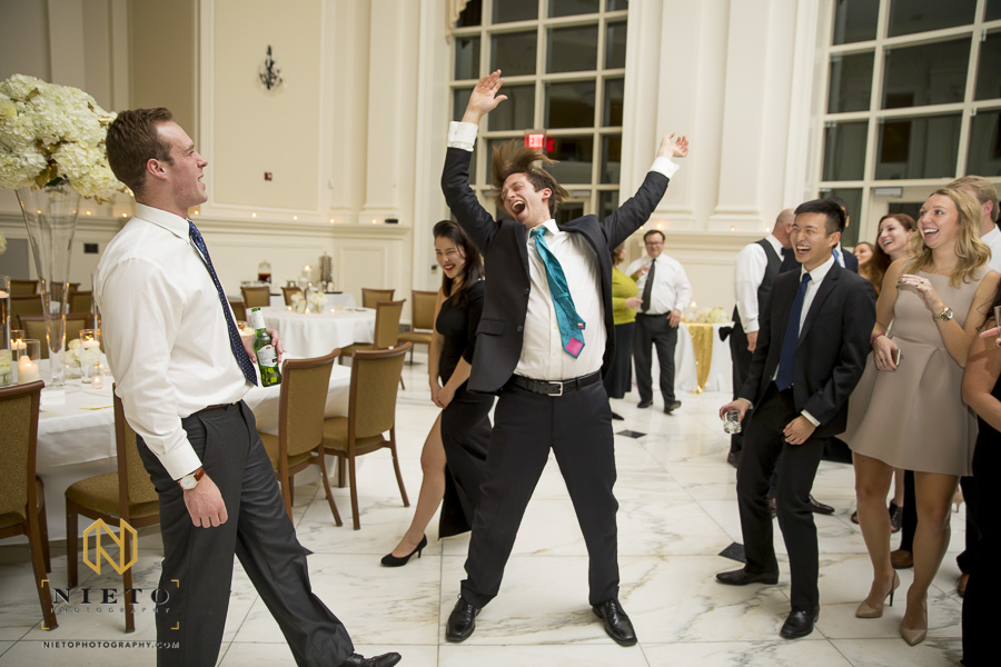 wedding guest going crazy on the dance floor as people around him smile and laugh