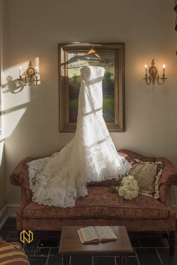 wedding gown hanging in front of painting at Hayes Barton Baptist Church