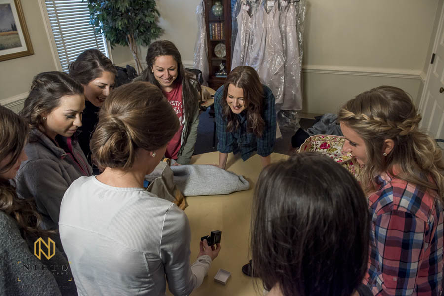 bride showing her bridesmaids her wedding band