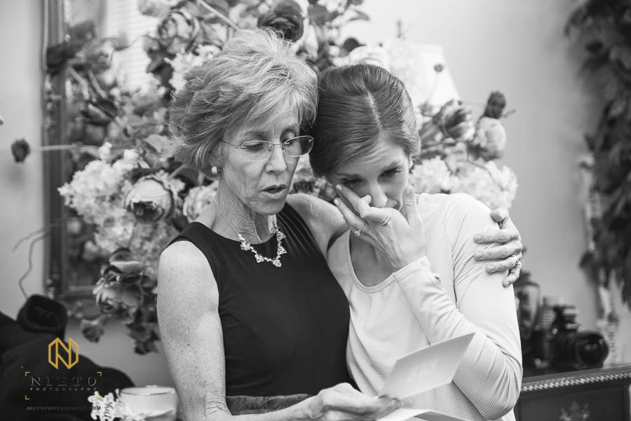 black and white image of bride crying as her mother reads a note