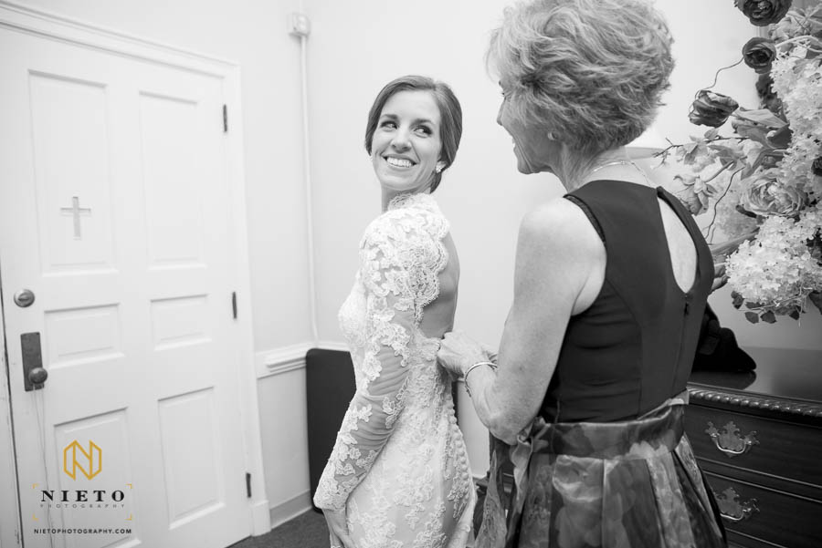 bride looking back at her mother as she buttons the back of her dress