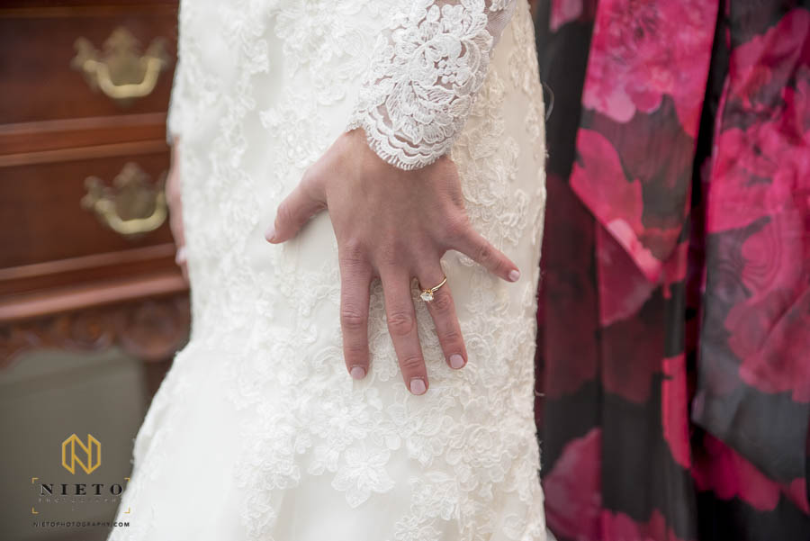 brides hand with her engagement ring against her dress