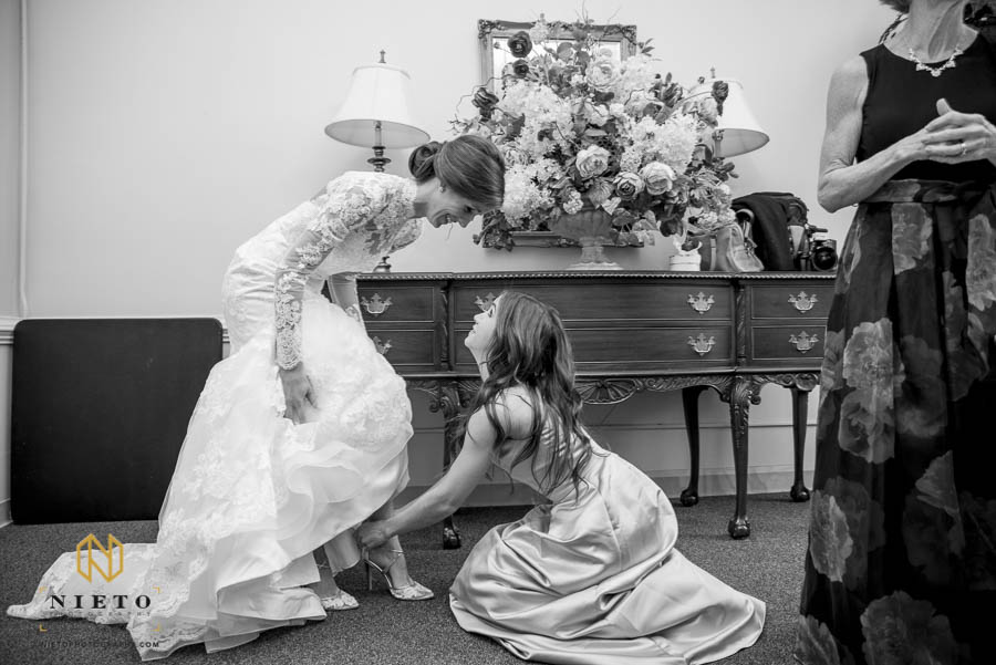 The bride and her sister talking as the sister helps her put her shoes on