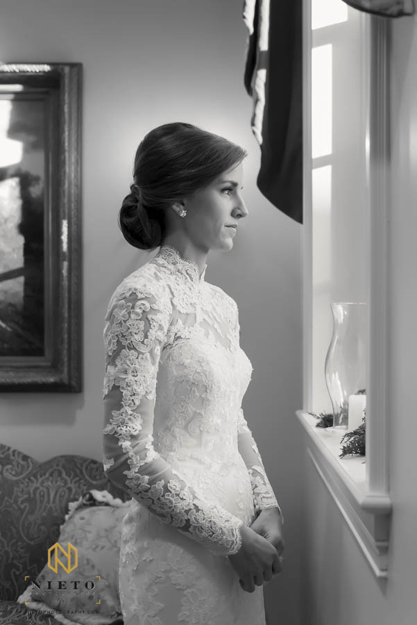 black and white portrait of the bride in her gown looking out the window at her Hayes Barton Baptist Church wedding