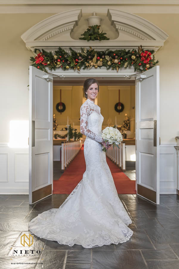 bride smiling at camera as she stands in Hayes Barton Baptist Church