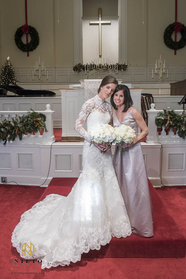 Bride and her sister posing for formal portrait in side the chapel at hayes barton baptist church
