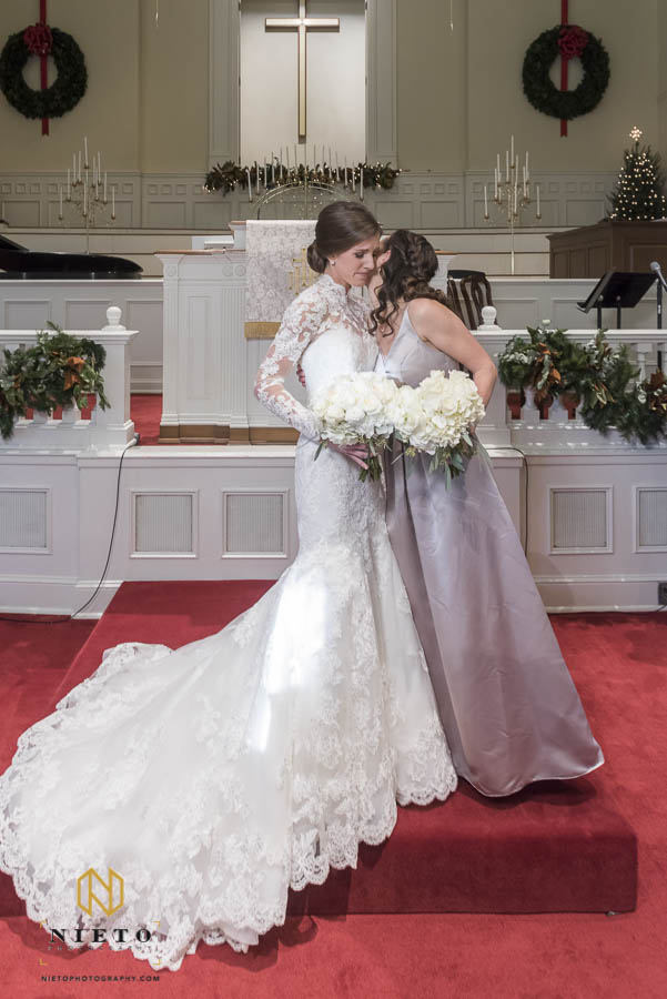 bridesmaid kissing the bride during formal portraits in the chapel of hayes barton baptist church