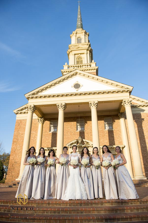 bridal party smiling at the camera in front of Hayes Barton Baptist Church