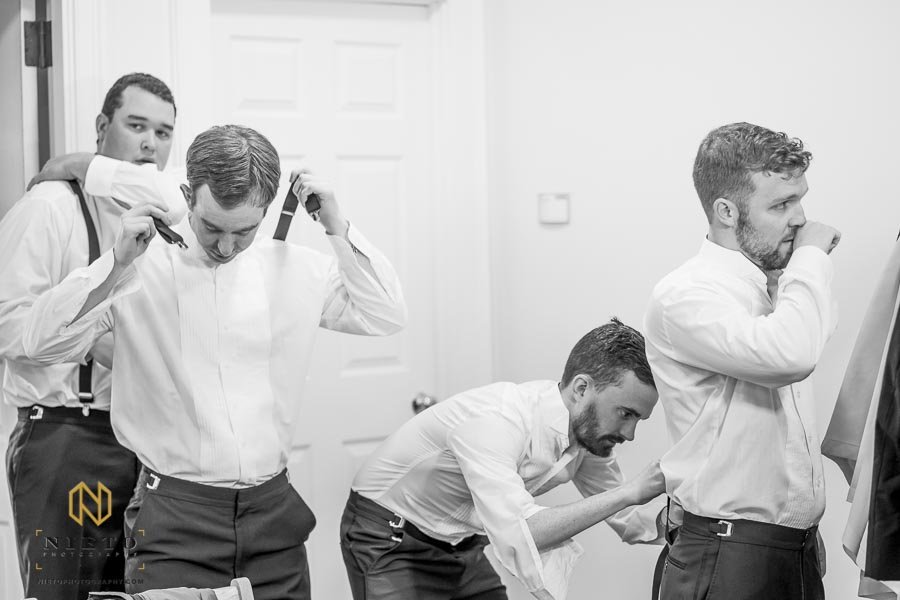 black and white candid image of groomsmen getting their tuxedoes on