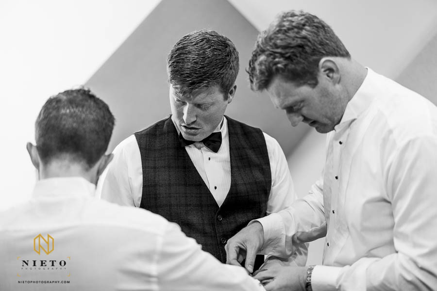 groomsmen helping the groom with his cufflinks