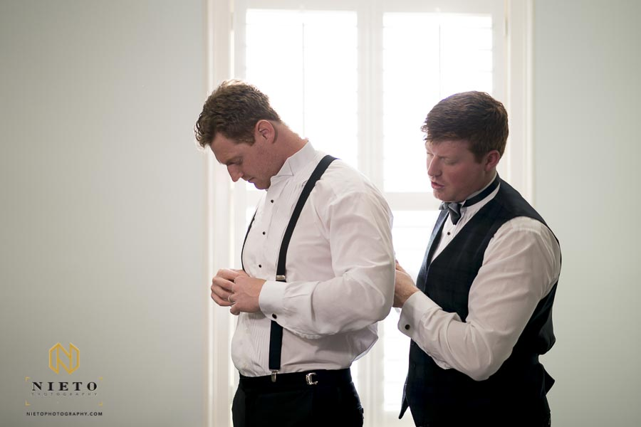 groom helping his brother with his suspenders