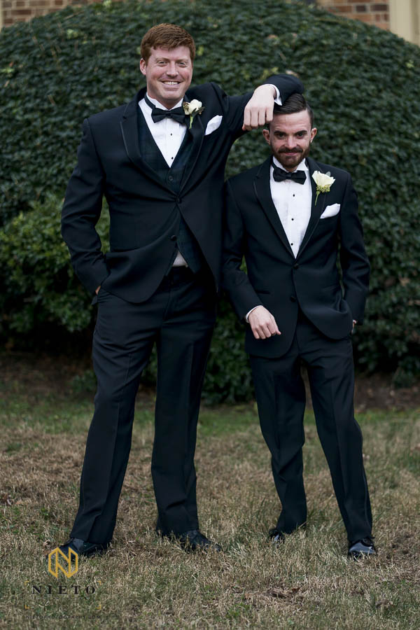 groom leaning on a shorter groomsman during formal portraits