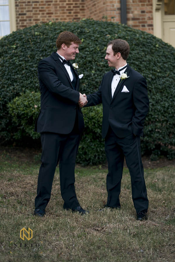 groom and groomsman shaking hands during formal portraits