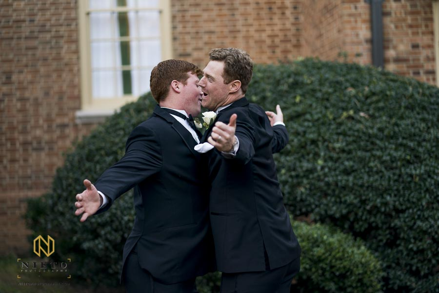 groom and brother chest bumping in their tuxes