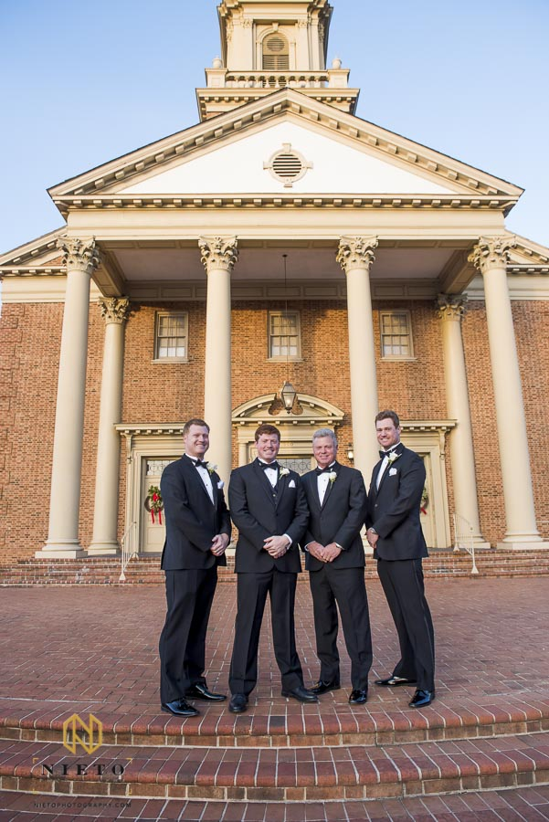 groom posing with his brothers and father in front of Hayes Barton Church