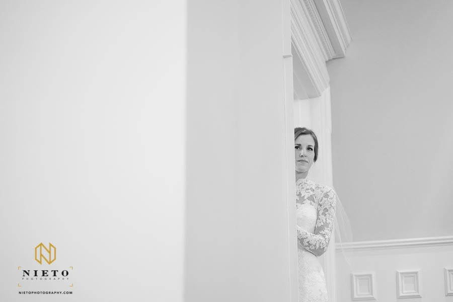 Bride taking a peek from the balcony at her ceremony