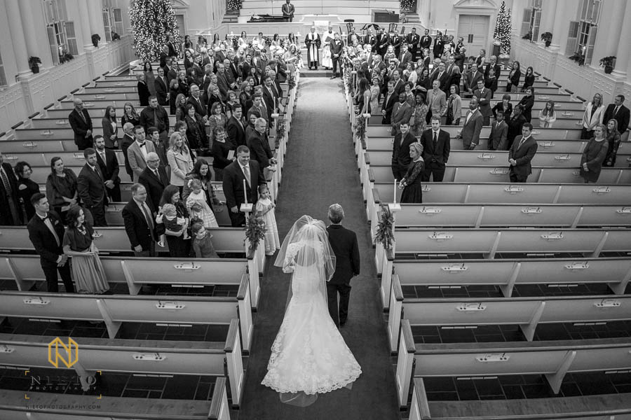 wide black and white shot of the bride walking down the aisle towards the alter