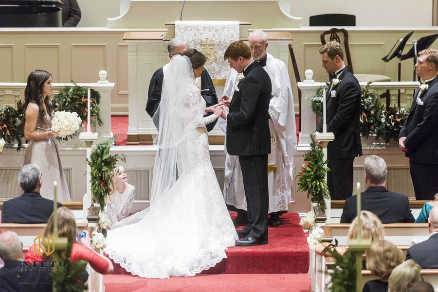 groom placing the wedding band on the brides finger during their Hayes Barton Baptist Church wedding