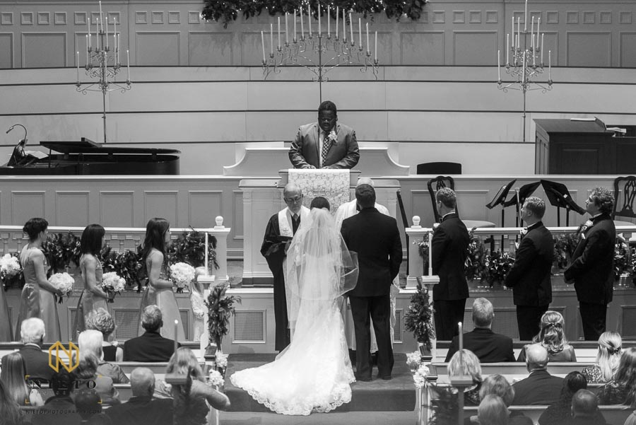 bride and groom at the altar with the ministers during the wedding ceremony at Hayes Barton Baptist Church