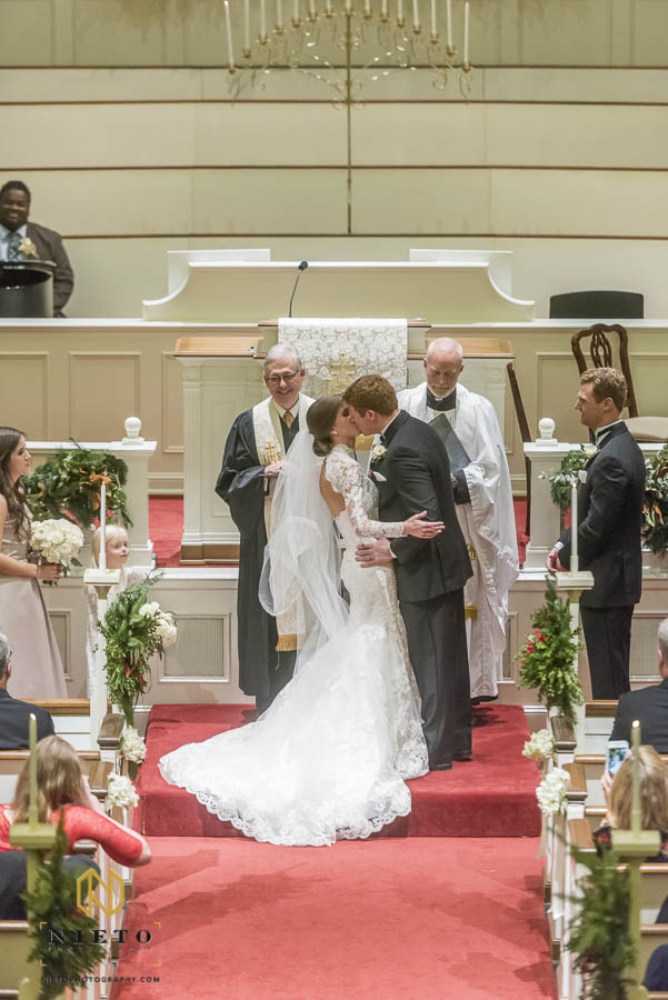 Bride holding on to groom as they kiss for the first time at their wedding ceremony