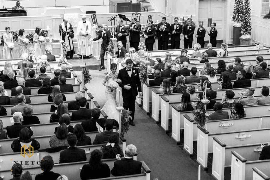 black and white image of the bride and groom recessing down the aisle