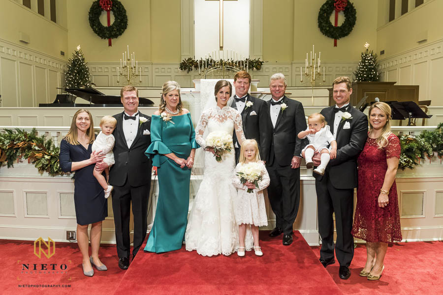 bride posing with groom and his family at church altar