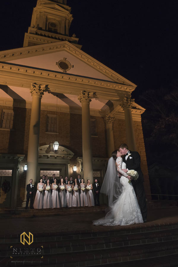 Bride and groom kissing in front of Hayes Barton Baptist Church with the wedding party behind them