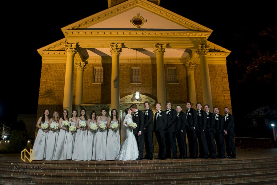 bride kissing as wedding party posing for portrait in front of Hayes Barton Baptist Church