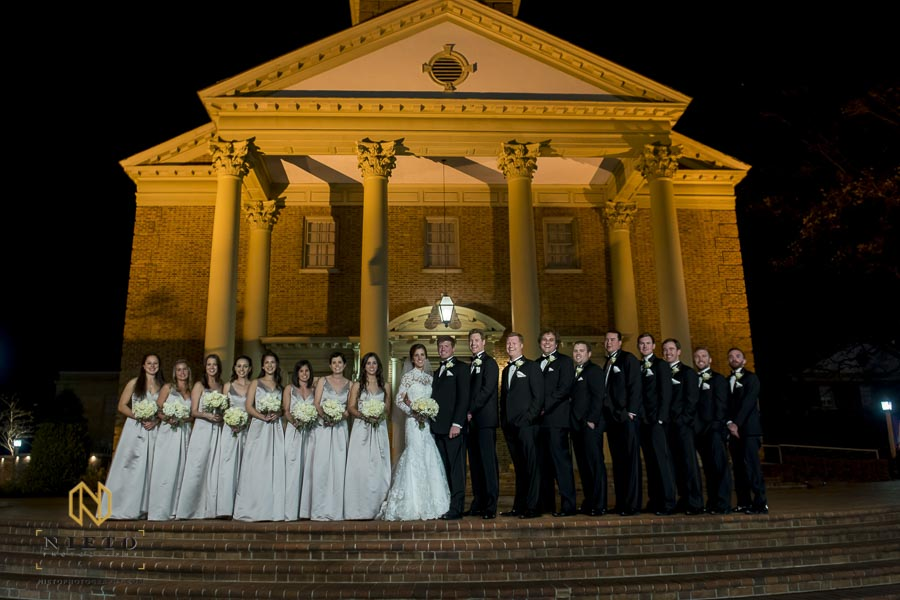wedding party posing for portrait in front of Hayes Barton Baptist Church at night