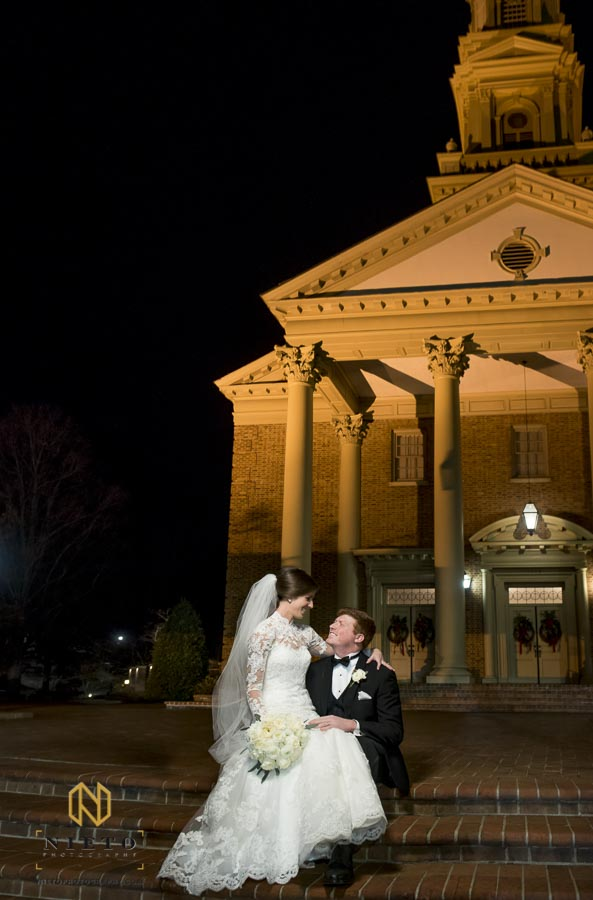 bride and groom sitting in front of Hayes Barton Baptist Church at night